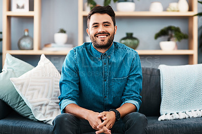 Buy stock photo Cropped portrait of a handsome young man smiling while sitting on a couch in his living room at home