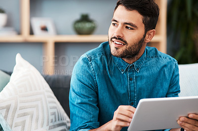Buy stock photo Cropped shot of a handsome young man looking thoughtful while using a digital tablet in his living room at home