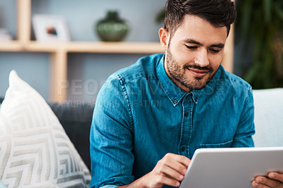 Buy stock photo Cropped shot of a handsome young man looking cheerful while using a digital tablet in his living room at home