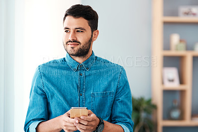 Buy stock photo Cropped shot of a handsome young man looking thoughtful while using a mobile phone in his living room at home