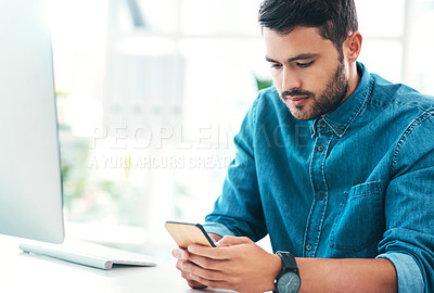 Buy stock photo Cropped shot of a handsome young businessman using a mobile phone while sitting in an office
