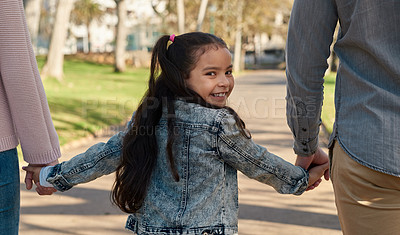 Buy stock photo Shot of an adorable little girl going for a walk in the park with her parents