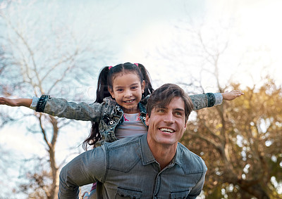 Buy stock photo Shot of an adorable little girl enjoying a piggyback ride with her father at the park