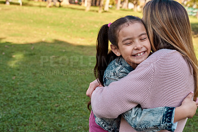 Buy stock photo Shot of an adorable little girl embracing her mother at the park