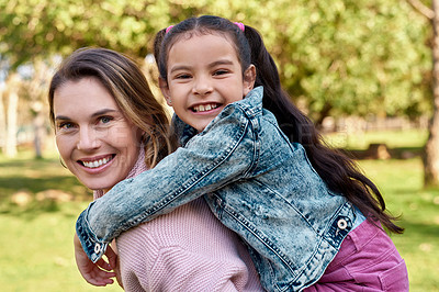Buy stock photo Shot of an adorable little girl enjoying a piggyback ride with her mother at the park