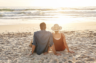 Buy stock photo Rearview shot of a middle aged couple watching the sunset on the beach