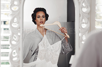 Buy stock photo Cropped shot of a woman holding her wedding dress against her while looking in the mirror