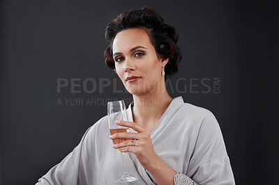 Buy stock photo Cropped shot of a woman drinking champagne while getting ready