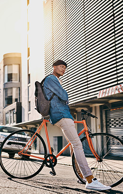 Buy stock photo Shot of a handsome young man out in the city with his bicycle
