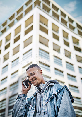 Buy stock photo Shot of a handsome young man using his cellphone while out in the city