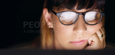 Buy stock photo Shot of a young businesswoman looking bored while using a computer during late night at work