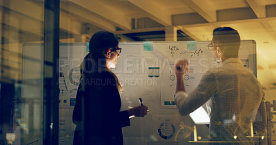 Buy stock photo Cropped shot of two business colleagues standing and using a whiteboard and technology to brainstorm in the office at night