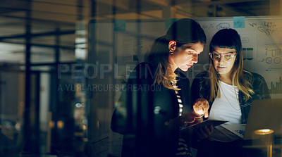 Buy stock photo Cropped shot of two attractive young businesswomen standing together and using technology to brainstorm in the office at night