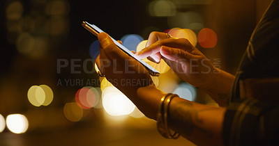 Buy stock photo Cropped shot of an unrecognizable businesswoman standing alone and texting on her cellphone while outdoors at night