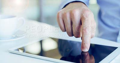 Buy stock photo Cropped shot of an unrecognizable businessman sitting alone and typing on his tablet in the office