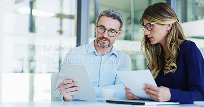 Buy stock photo Cropped shot of two business colleagues sitting together and using technology and paperwork during a discussion in the office