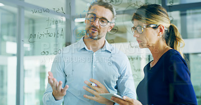 Buy stock photo Cropped shot of two business colleagues using technology and a clear board to brainstorm while standing together in the office