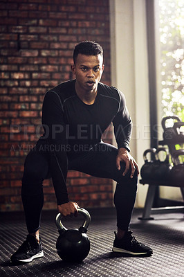 Buy stock photo Shot of a young man working out with a kettle bell in a gym