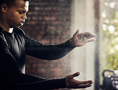 Buy stock photo Shot of a young man dusting his hands with chalk powder at the gym