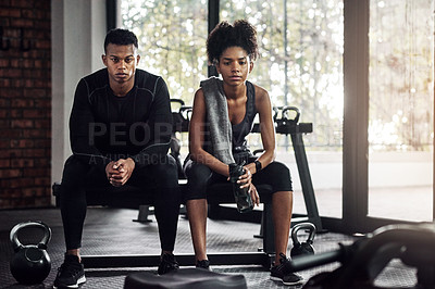 Buy stock photo Shot of a young man and woman sitting on a bench during a break at the gym