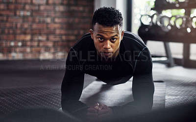 Buy stock photo Shot of a young man doing plank exercises in a gym