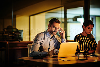 Buy stock photo Shot of a mature businessman working on a laptop in an office at night with his colleague in the background