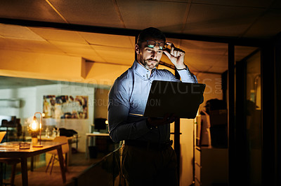 Buy stock photo Shot of a mature businessman using a laptop in an office at night
