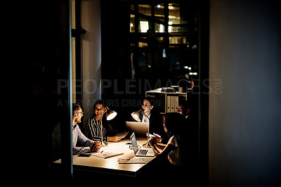 Buy stock photo Cropped shot of a diverse group of businesspeople sitting together and having a meeting in the office late at night