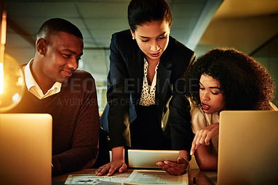 Buy stock photo Cropped shot of a diverse group of businesspeople working with technology during a meeting in the office late at night