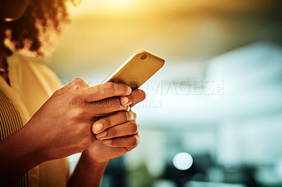 Buy stock photo Cropped shot of an unrecognizable businesswoman standing alone in her office and texting on her cellphone late at night