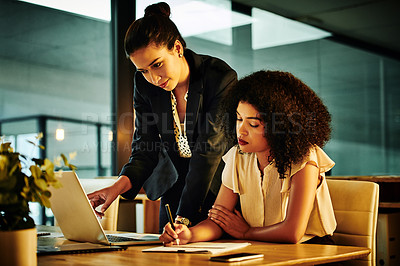 Buy stock photo Cropped shot of an attractive young businesswoman dictating notes to her colleague in the office at night