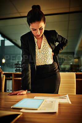 Buy stock photo Cropped shot of an attractive young businesswoman suffering from back pain while working in the office late at night