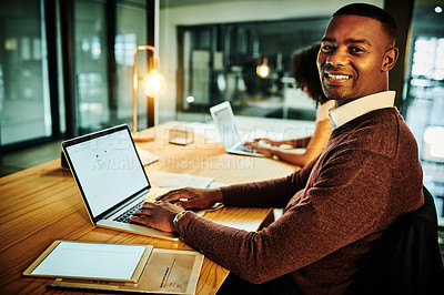 Buy stock photo Cropped shot of a handsome young businessman sitting with his colleague and using his laptop in the office at night