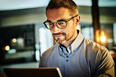 Buy stock photo Shot of a mature businessman using a digital tablet in an office at night