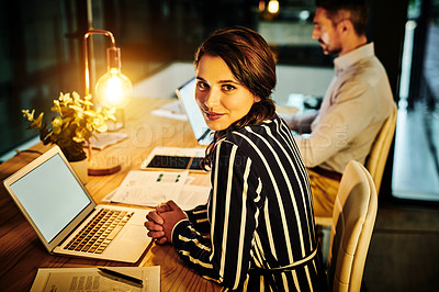 Buy stock photo Portrait of a young businesswoman working in an office at night with her colleague in the background