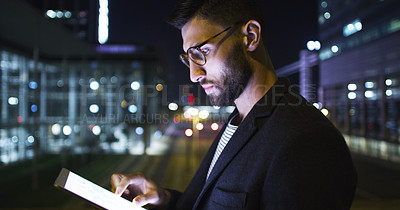 Buy stock photo Cropped shot of a handsome young businessman standing alone and using a tablet in the office late at night