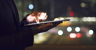 Buy stock photo Cropped shot of an unrecognizable businessman standing alone and using a tablet late at night in the office