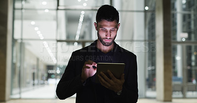Buy stock photo Cropped shot of a handsome young businessman standing and using a tablet after working a late shift in the office
