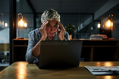 Buy stock photo Shot of a mature male doctor suffering from a headache while working on a laptop inside his office at night