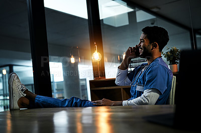 Buy stock photo Shot of a handsome young doctor making a phone call inside his office at night