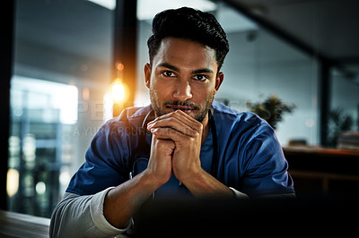 Buy stock photo Portrait of a handsome young doctor working in his office at night