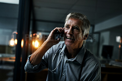 Buy stock photo Shot of a mature male doctor making a phone call inside his office at night