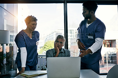 Buy stock photo Shot of a group of medical professionals working on a laptop together inside an office at a hospital