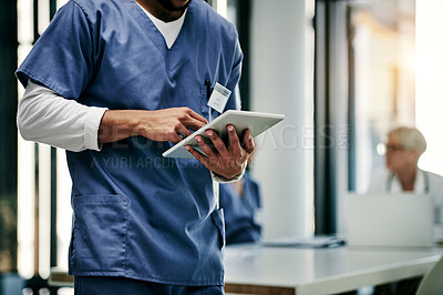Buy stock photo Shot of an unrecognizable nurse using a digital tablet inside a hospital