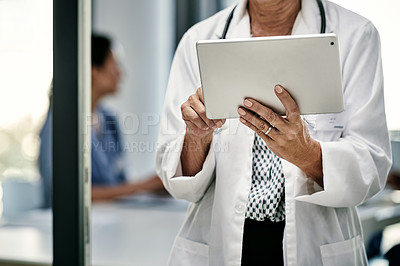 Buy stock photo Shot of an unrecognizable female doctor using a digital tablet inside a hospital with her colleagues in the background