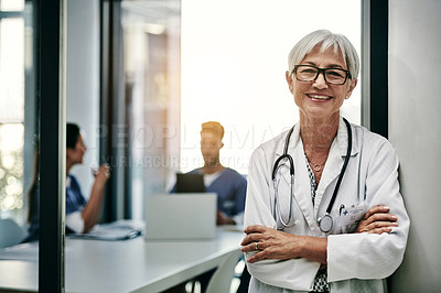 Buy stock photo Portrait of a mature female doctor posing with her arms folded inside a hospital with her colleagues in the background