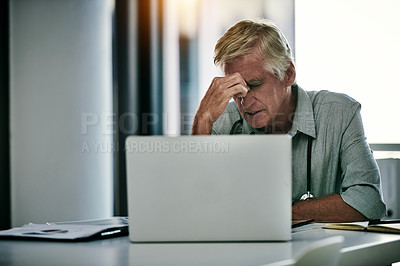 Buy stock photo Shot of mature male doctor looking stressed out while working on a laptop inside his office