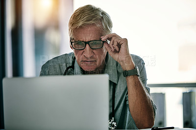Buy stock photo Shot of a mature male doctor working on a laptop inside his office
