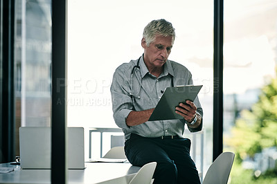 Buy stock photo Shot of a mature male doctor working using a digital tablet inside his office