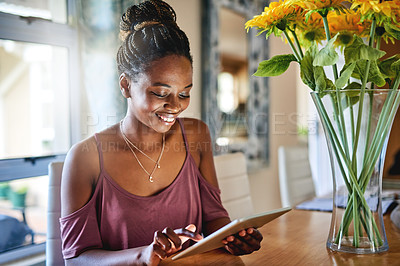 Buy stock photo Shot of a young woman using a digital tablet while sitting at home